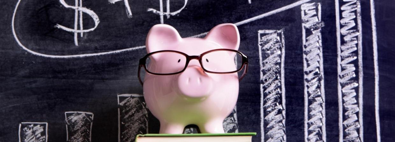 Spaarvarken met bril op een stapel boeken