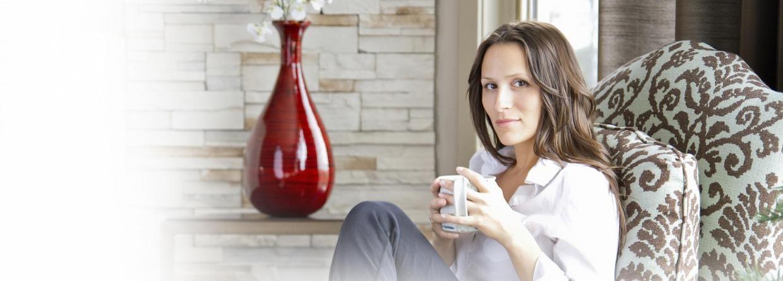 Vrouw zit op een stoel met een beker in haar hand