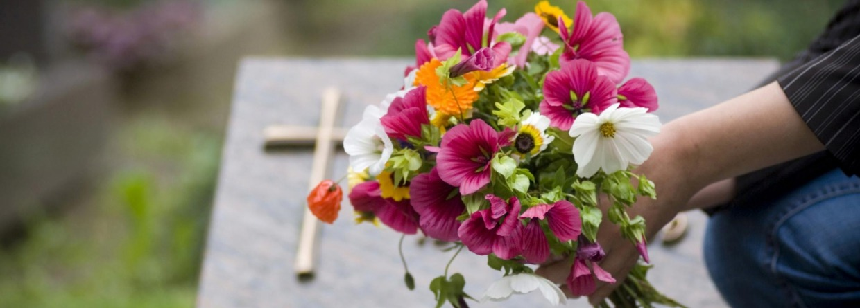 Vrouwenhand die een bos bloemen op een graf legt