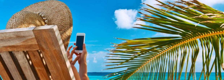 Vrouw in strandstoel met mobiel