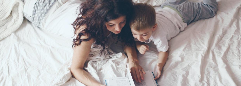 Moeder en zoon liggen op bed een boek te lezen