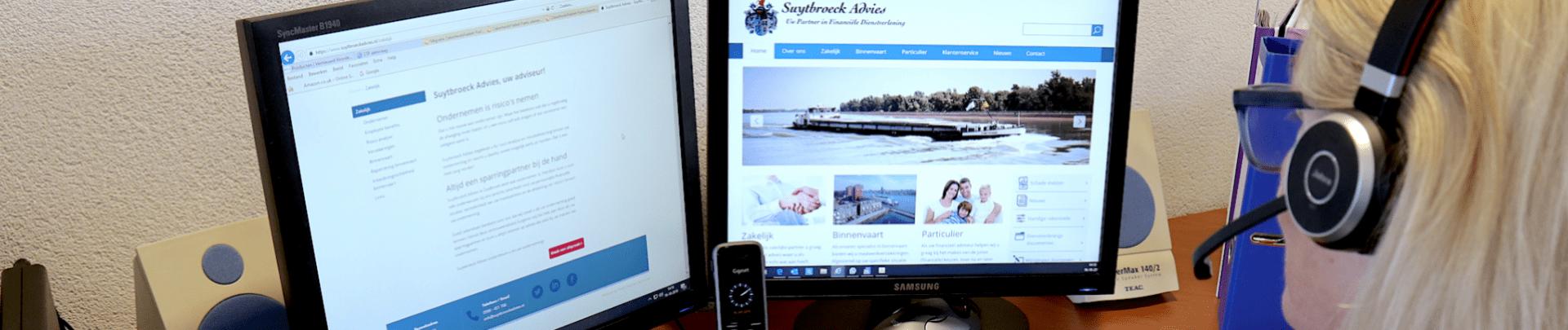 Vrouw achter beeldscherm met de site van Suytbroeck Advies in beeld
